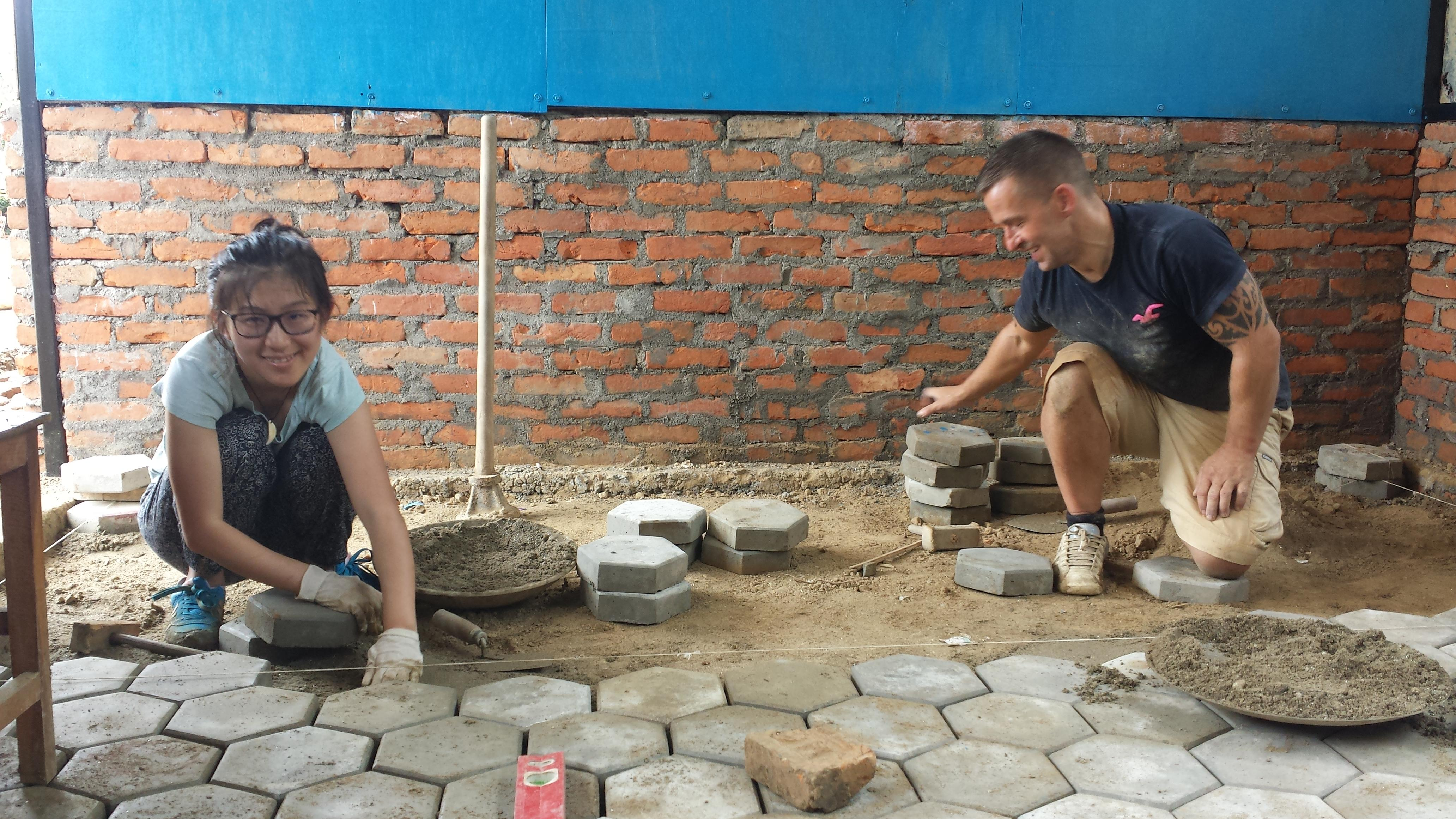 Projects Abroad volunteers assist in laying concrete slabs whilst on their building volunteer work in Nepal.